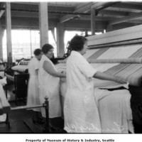 1935 Women using steam press for laundry work